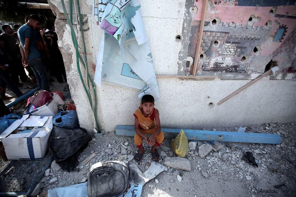 En gutt sitter i ruinene av en UNRWA-skole på Gazastripen.